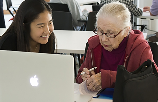Young woman helping elder woman on computer